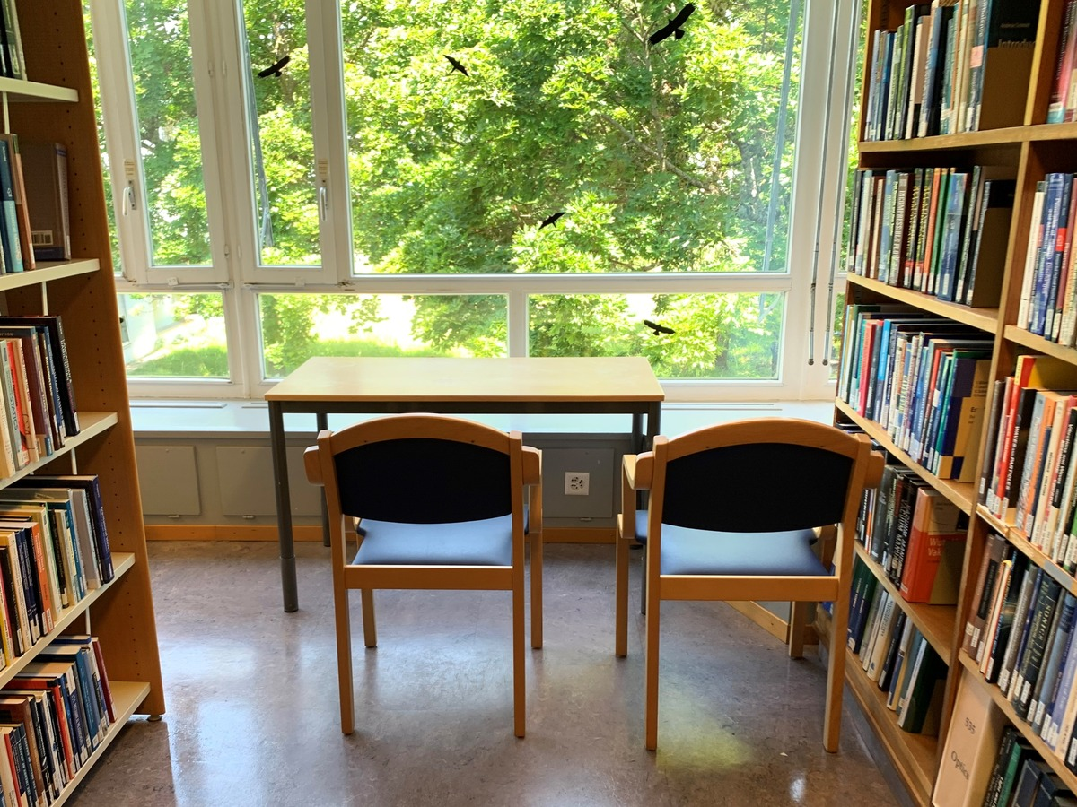 An image of the library with a desk a two chairs.